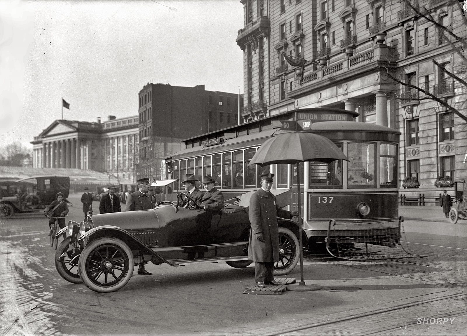 """District of Columbia, 1913. Traffic Stop and Go signs."" Traffic safety in Washington with the Treasury building at left. Note the pedestrian-catcher on the streetcar. Harris & Ewing Collection glass negative."