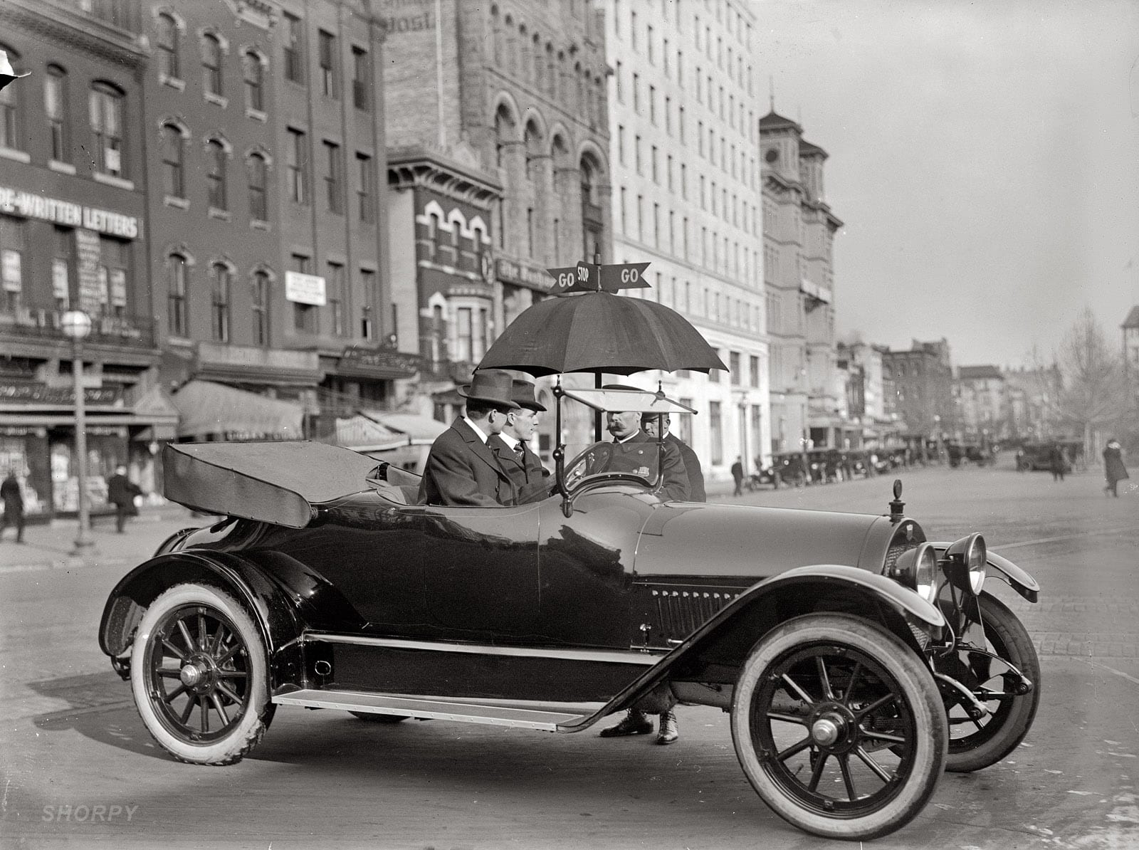 "1913. ""District of Columbia traffic. Stop and Go signs."" A very new-looking circa 1913 Haynes roadster in Washington crossing Pennsylvania Avenue at 14th Street N.W. Harris & Ewing Collection glass negative."