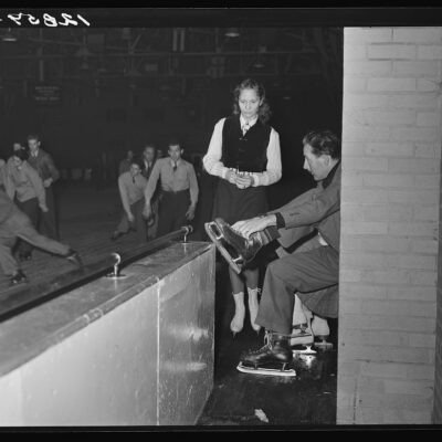 Chevy Chase Ice Palace, Washington. D.C. Skater fastening on skates while companion watches