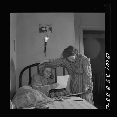 Two girls looking at pictures in their room in a boardinghouse