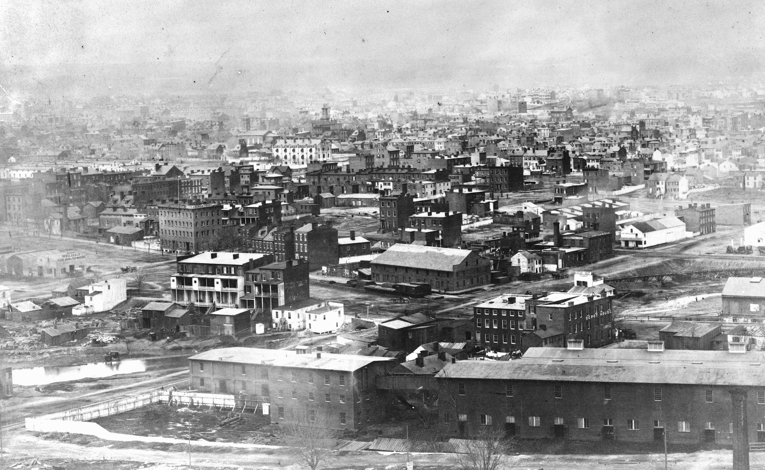 Early photographic view of Washington, D.C. from Capitol Hill, looking northwest - Northwest view with 1st, B, C, D streets, and Indiana Ave. in the foreground; view includes the Washington Jail, Aldrich's Wholesale Flour, Grain & Feed Warehouse, Dyers American House, Shamokin & Lykins Valley Coal (Wood & Coal), Depot House, C. Boyle, and Door, Sash & Blind Factory