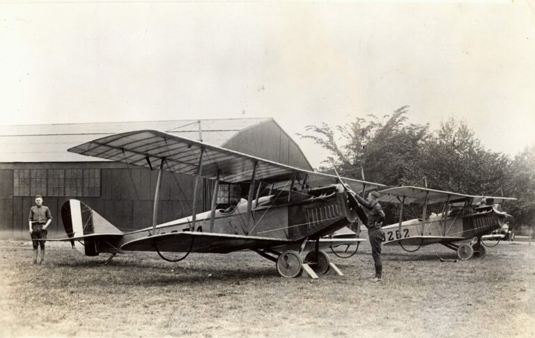 """Two Curtiss JN-4H """"Jenny"""" airmail planes parked at the temporary airmail field at Washington, DC's Polo Field, a small strip of grassy land between the Tidal Basin and Potomac River."""