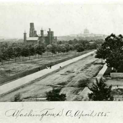 View of the Smithsonian Institution Building looking east up B Street (Independence Ave) towards the U.S. Capitol. Grounds are landscaped following a plan laid out by Andrew Jackson Downing, with the Castle nestled among trees. Visible amidst the trees is the Magnetic Observatory, built in 1853. People stand along the fence installed along the sidewalk on B Street In this image, the central roof of the Castle is intact and the small towers have the caps on them. In January of 1865, a fire destroyed the central roof and the caps on the towers, so this photograph had to have been taken prior to January 1865 and is most likely April 1863. The Capitol dome, seen in the distance, is not yet completed