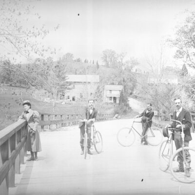 Three men with bicycles on bridge near Pierce Mill, Washington, D.C.