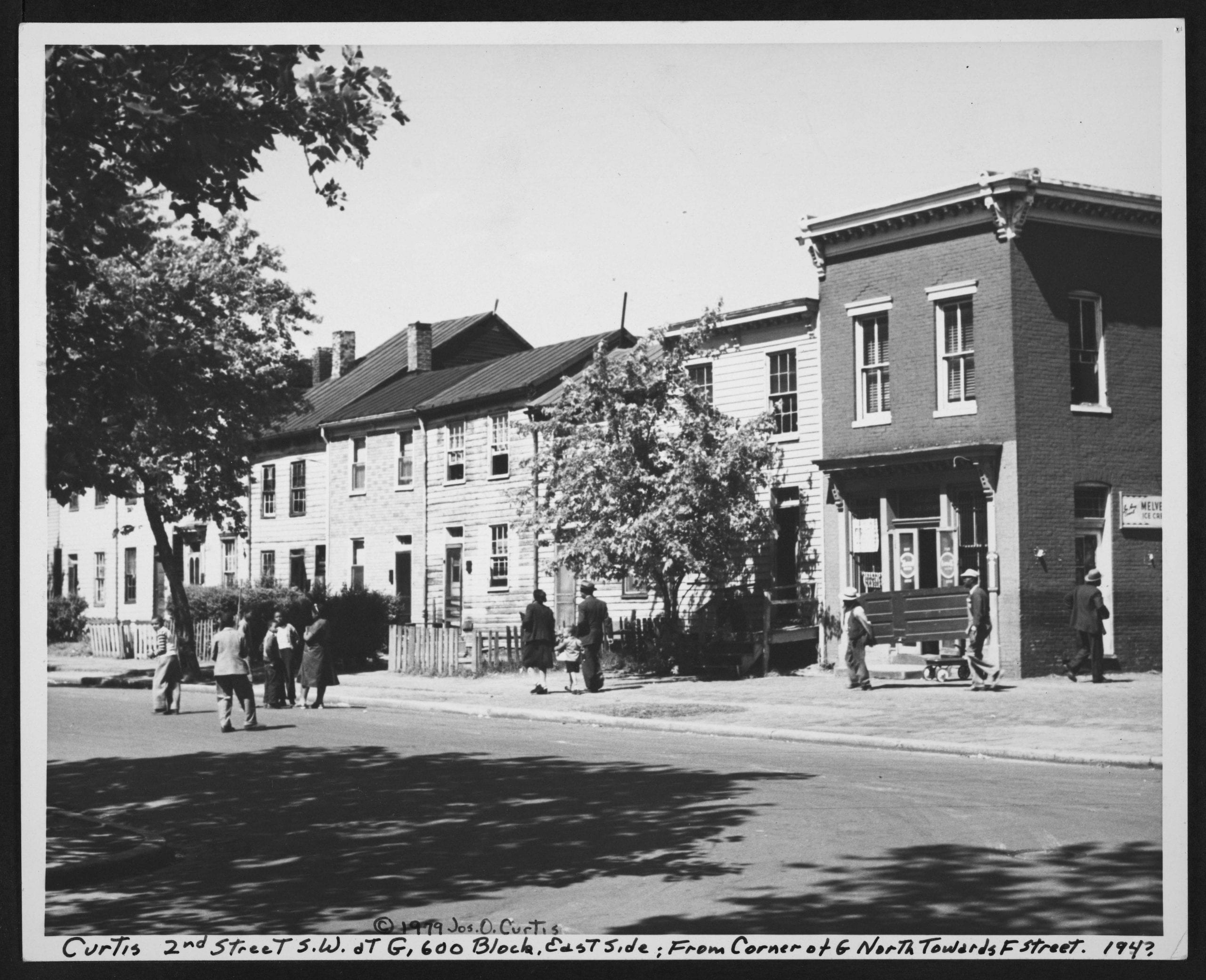 Street, row houses and corner store on the east side of the 600 block of G Street, looking north toward F Street. People walk and socialize on the sidewalk. Men carry a door.