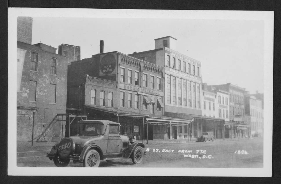 "View of commercial building on the northeast corner of B Street (later Constitution Avenue) and 7th Street NW. An automobile in the foreground has an Esso advertising cover on its spare tire that reads, ""ESSO THE GIANT POWER FUEL."" - February 1st, 1931"