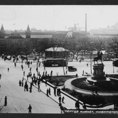 Expansive view of Center Market taken from an elevated position on the northeast corner of Indiana Avenue and 7th Street NW. A statue of Major General Winfield Scott Hancock is prominnent on the right side of the image which also features pedestrians, streetcars, horse and carriages, bicycles, and automobile traffic.