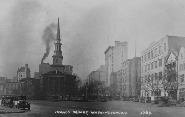 View looking west on New York Avenue NW from 13th Street and taking in the New York Avenue Presbyterian Church and the commercial buildings on H Street NW between 13th and 14th Streets. The time on the church steeple clock is 10:55 a.m.