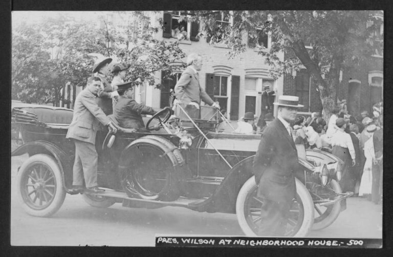 """Woodrow Wilson stands in the front of a convertible automobile stopped in the intersection of what was then N and Union Streets SW. Wilson, the driver of the car, and two woman in the back look east at something happening on N Street. A crowd gathered under a tree near the car and people in front of 485 N Street also look in the same direction. Two Secret Service agents look at the photographer. Written on the reverse is """"Barney Neighborhood House, 470 N Street SW."""" Wilson had only been President of the US for two months when the photo was taken."""