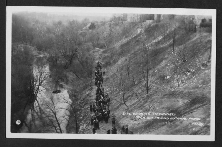View of a group of hikers walking alongside Rock Creek to the left and an embankment that leads up to the right upon which can be seen a row of buildings. Location is to the west and downhill from the 2800 block of Adams Mill Road NW.
