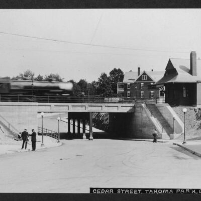 View looking from the northwest corner of Cedar and 4th Street NW east down Cedar Street toward the railroad underpass. Image includes a partial view of the Baltimore & Ohio Railroad station on the right with a blurred locomotive crossing the underpass and going into the station. The train is headed toward Washington, D.C.