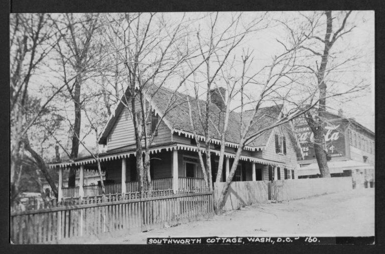 """View of the east and south elevations of Mrs. E. D. E. N (Emma Dorothy Eliza Nevitte) Southworth's cottage, located at the southwest corner of Prospect and 36th Streets NW. In background can be seen 1224 36th Street NW whose Prospect Street elevation is painted with """"Drink Coca-Cola."""""""