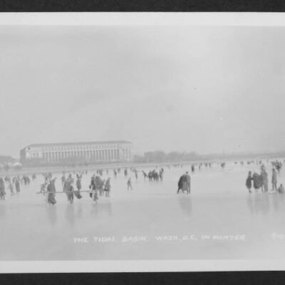 View looking east from the middle of a frozen Tidal Basin upon which many individuals are walking or skating. The Bureau of Engraving and Printing is visible in the distance.