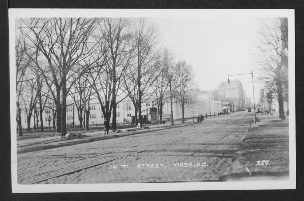 Looking north up 14th Street NW from just below Constitution Avenue NW. Visible is the Commerce Department and the Willard Hotel in the distance. A set of streetcar tracks appear embedded in the street in the foreground.