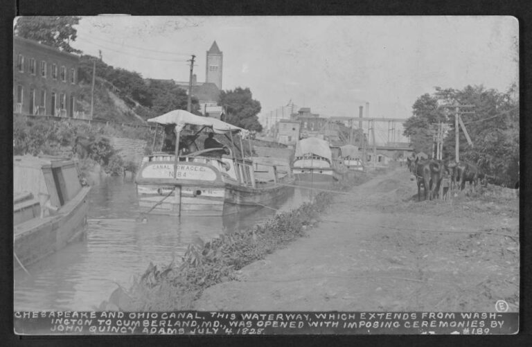 """View of four boats in the Chesapeake and Ohio Canal lined up to cross the Potomac Aqueduct Bridge. The boats are owned by the Canal Towage Co. (misspelled """"Towace). The postcard's reverse is stamped """"Sunday Magazine April 16, 1933."""""""
