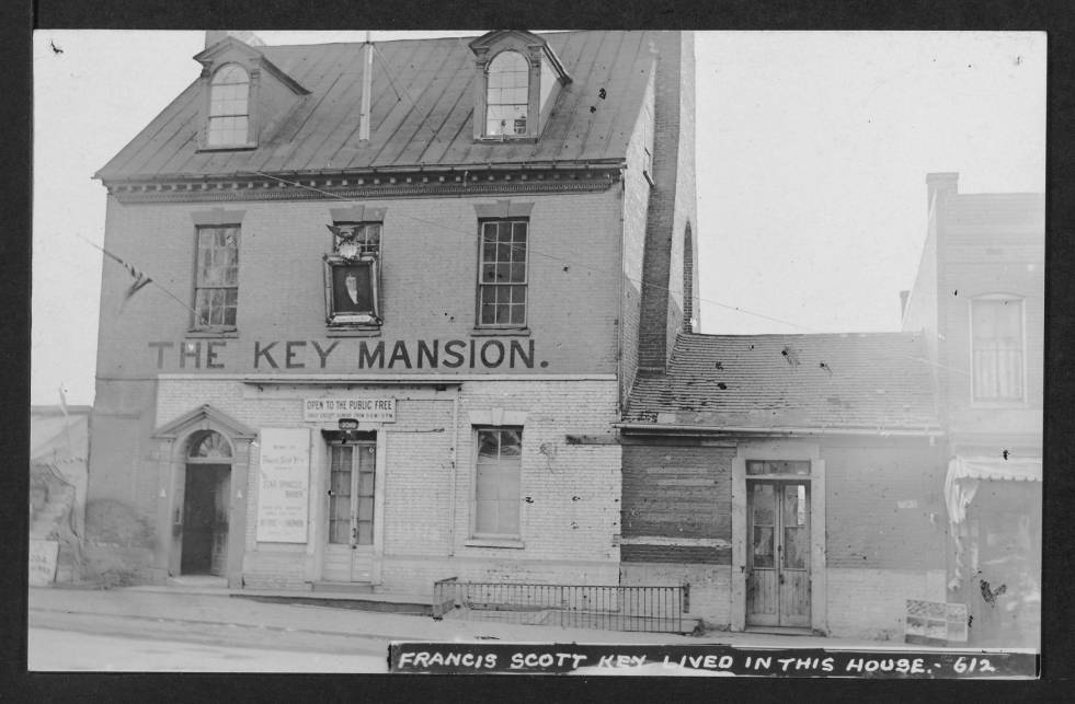 View of the M Street NW elevation of the two-story Key Mansion with Key's single-story law office attached to west side of structure. A portion of the commercial building continuing west along the street is also visible.