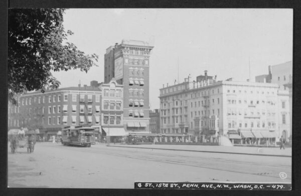 View from Pennsylvania Avenue NW looking east towards the buildings on the east side of 15th Street as well as the southeast corner of 15th and G Streets. Streetcars and horses and wagons are on streets.