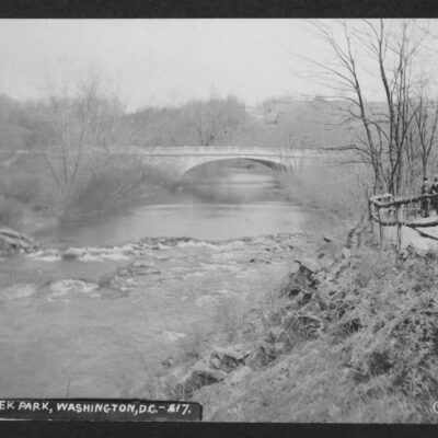 Wide view of the Old Harvard Street Bridge across Rock Creek Park taken from the south (down creek) side. A dirt road with a log fence appears on the right.