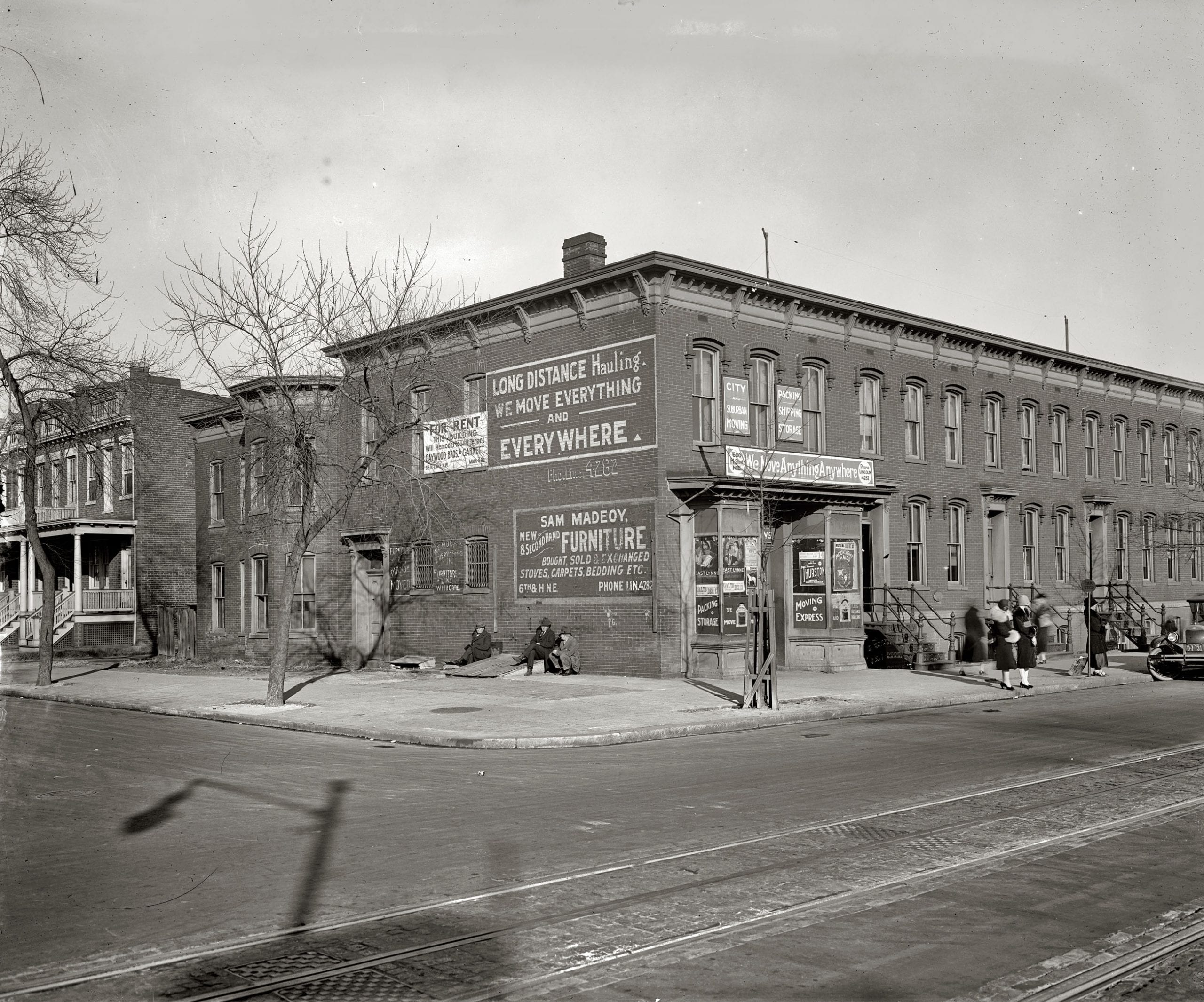 """Rowhouses and moving company."" Circa 1925, the furniture and hauling business of Sam Madeoy at 600 H Street N.E. National Photo Company."