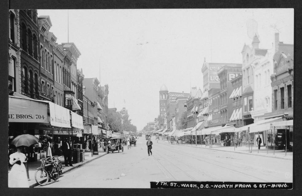 View looking north up 7th Street NW from G Street NW. Streetcars, automobiles and horse pulled carts are in the street.