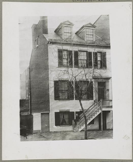 This 1861 photo of the Surratt house shows the raised door, first floor entry, and stairs.