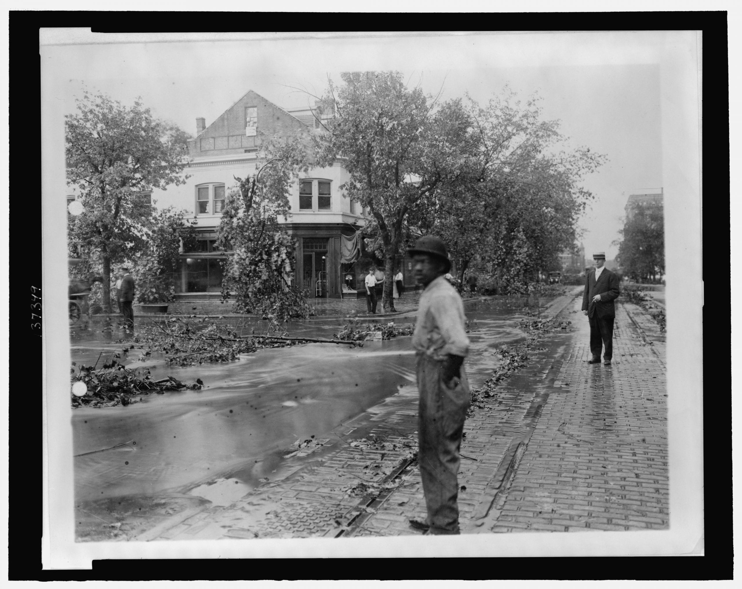Men standing looking at tree limbs and other debris and high water in the street after a storm