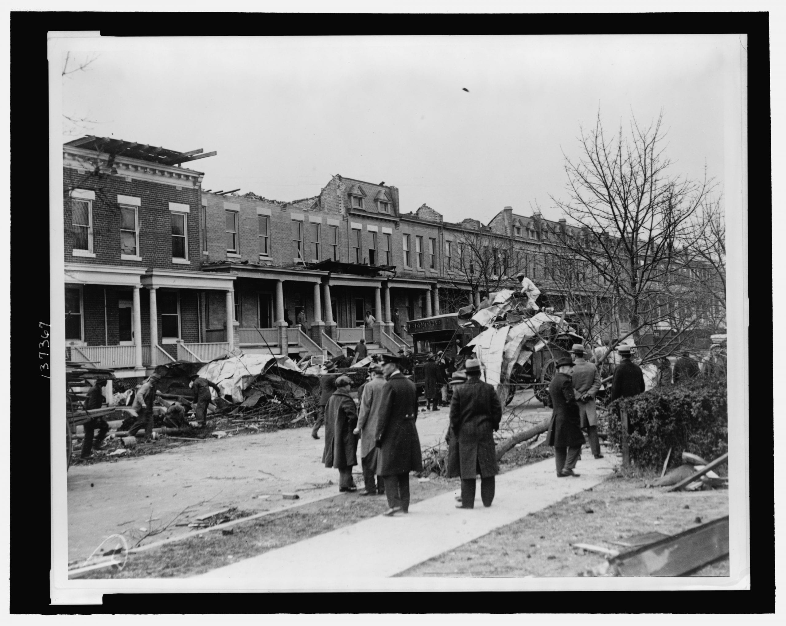 Men watching debris being cleaned up at row houses on A St., NE, near 14th St., severely damaged by a tornado on Nov. 17, 1927