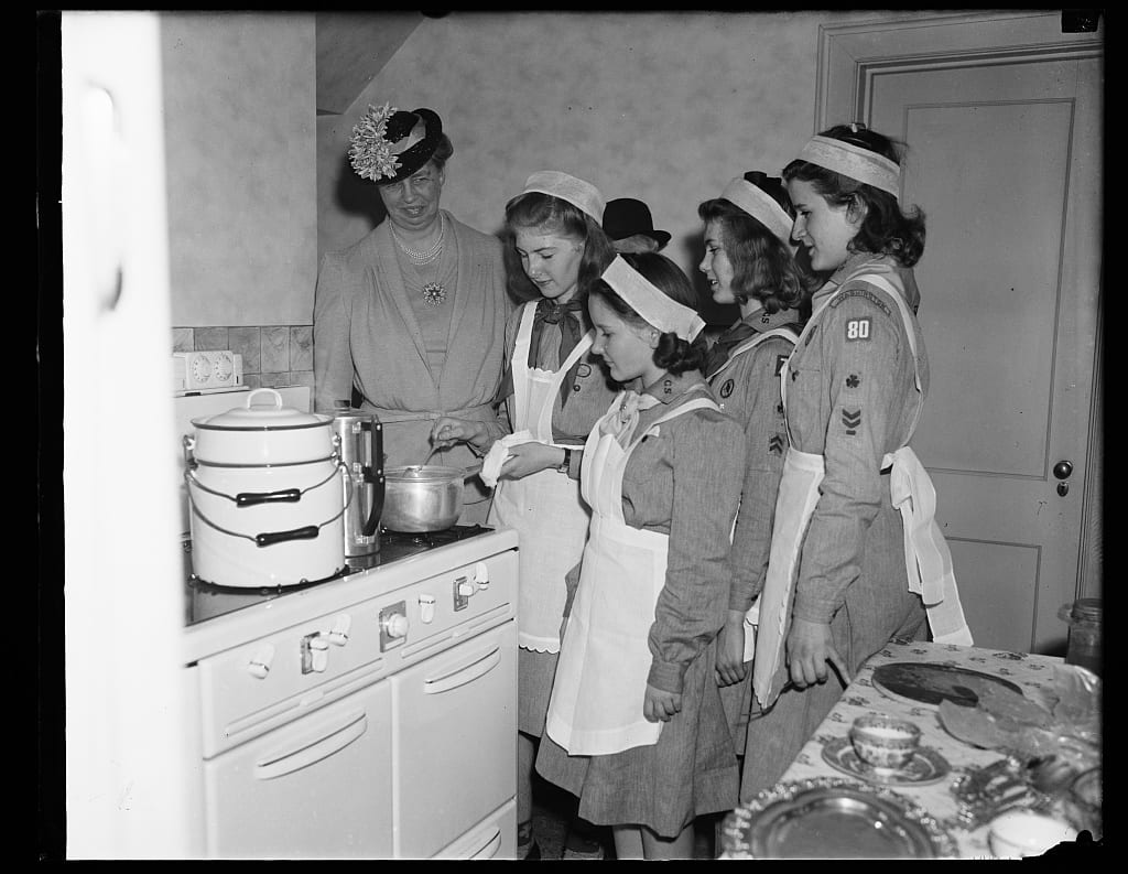 Eleanor Roosevelt watches on as the Scouts cook for a luncheon in 1940