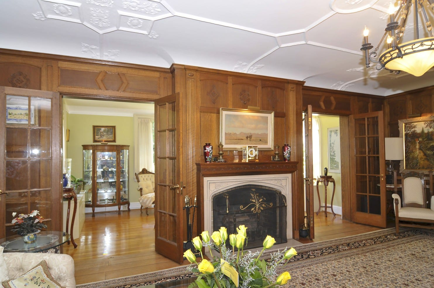 (Photo by HomeVisit) The living room has a cast stone fireplace with a chestnut mantel.