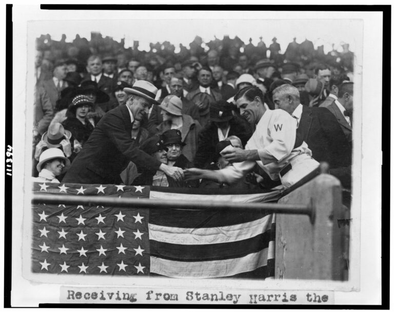Manager Stanley Harris, in the grandstand, presents President Coolidge with the baseball used to open the 1924 World Series (October 4th, 1924)