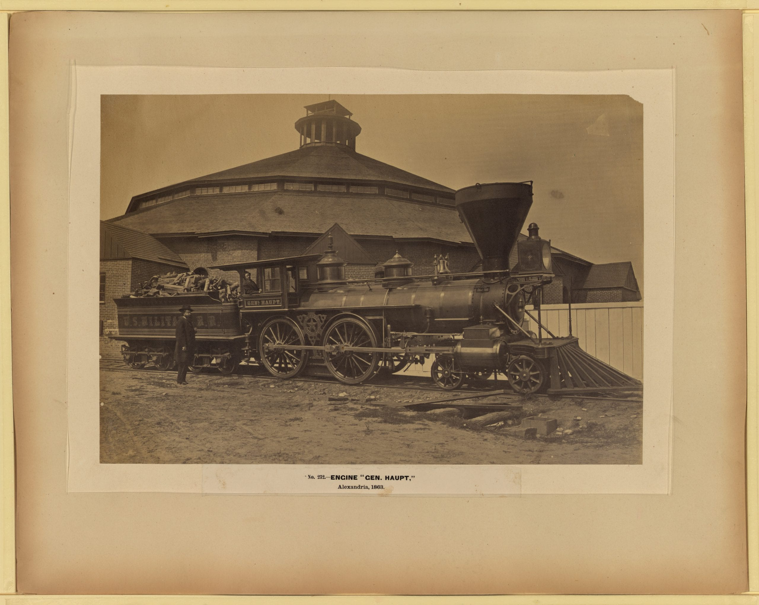 "Photograph shows wood burning locomotive ""Gen. Haupt"" named for Herman Haupt, chief of Construction and Transportation, in front of the roundhouse at the Alexandria station."
