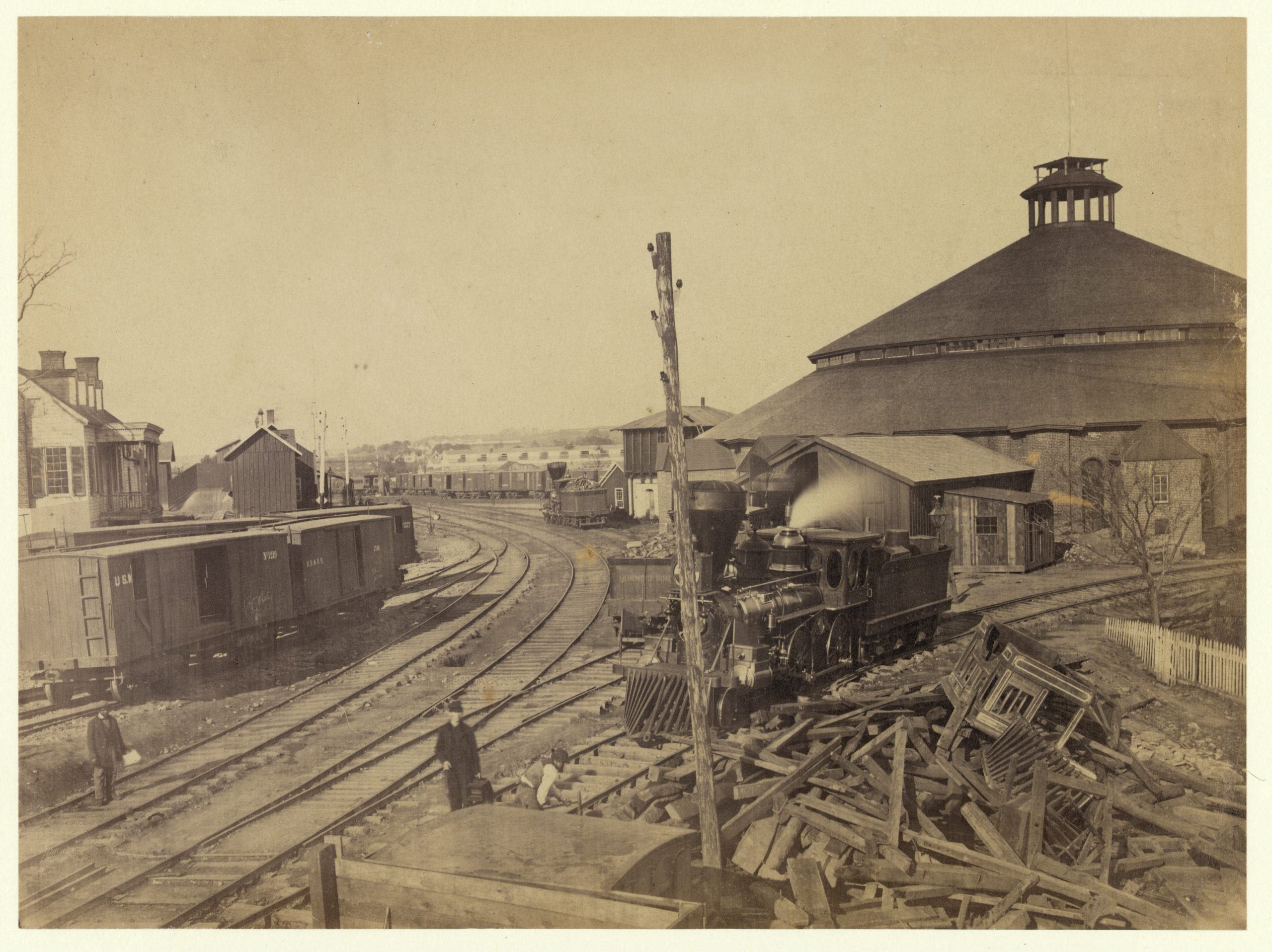 Photograph shows a locomotive moving away from the roundhouse at the Orange & Alexandria railroad yard in Alexandria, Virginia. Railroad signal lights on pole in foreground.