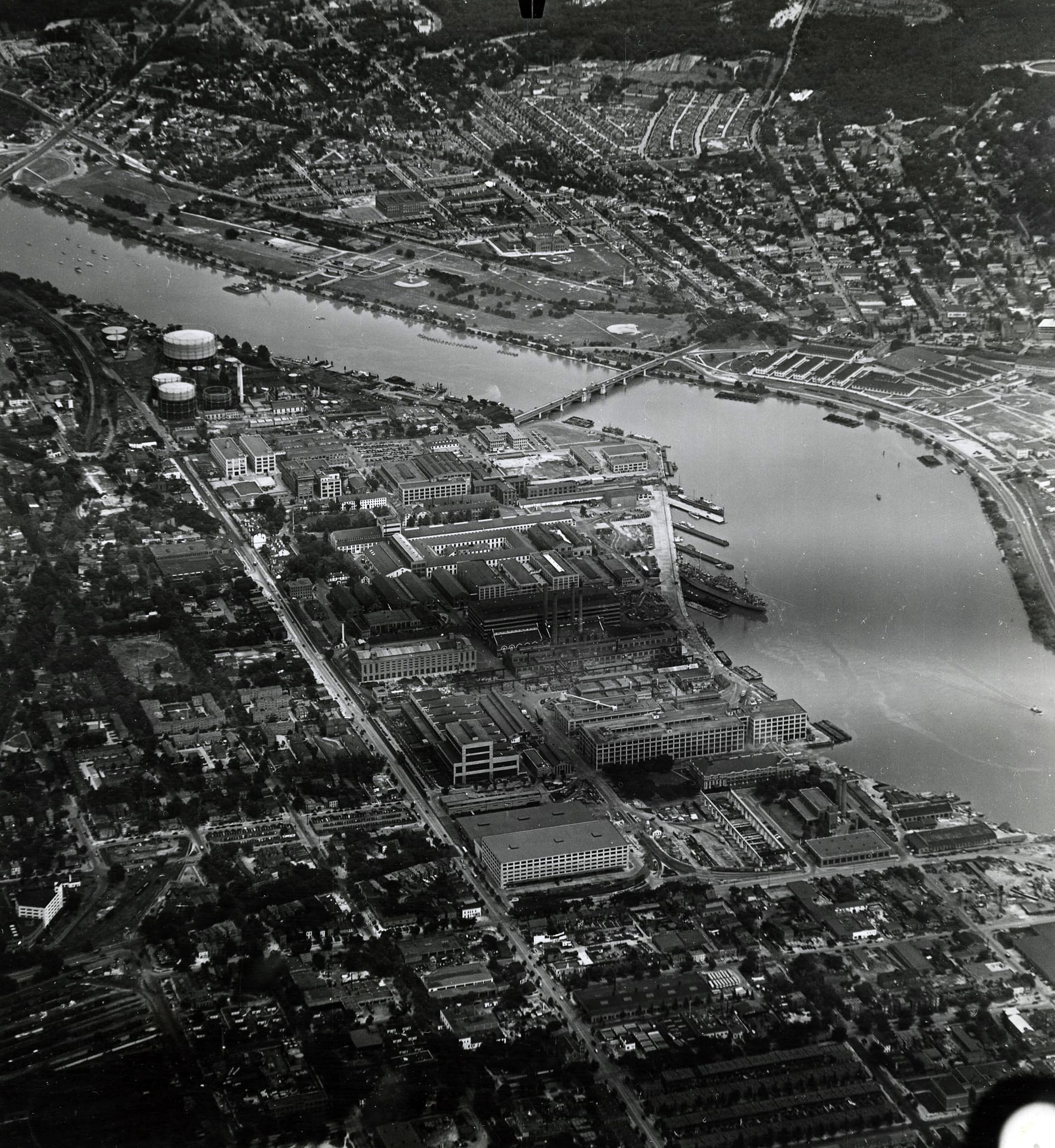 Aerial view, looking east, of the Washington Navy Yard, Washington, D.C., with the Anacostia River in the right view, circa mid-1980s. Note, USS Barry (DD 993) moored to the pier. NHHC Photograph Collection, Navy Subject Files, Washington Navy Yard. (221).