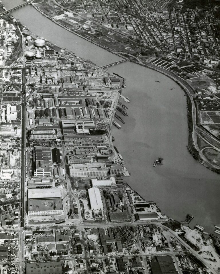 Aerial view of the Washington Navy Yard, looking east (top). This shot shows the Navy Yard's borders: M Street on the north (left); the waterfront on the south; 11th street on the east, and 2nd street on the west (foreground). On the right bank of the river is Anacostia, September 1963. NHHC Photograph Collection, Navy Subject Files, Washington Navy Yard. (214).