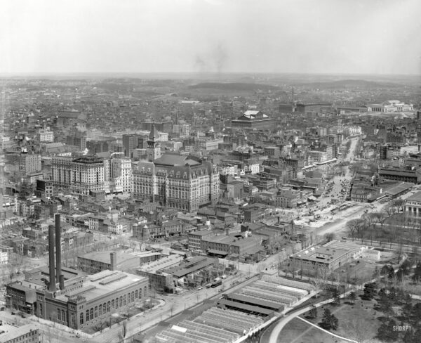 """Circa 1911. """"Washington from Washington Monument."""" Points of interest in this panoramic view include B Street (today's Constitution Avenue), running diagonally from the Potomac Electric powerhouse at lower left; Louisiana Avenue, branching off in the general direction of Union Station at upper right; the Old Post Office and its clock tower at left-center across Pennsylvania Avenue from the Raleigh Hotel under construction; the Agriculture Department greenhouses in the foreground with a corner of the Smithsonian """"National Museum"""" at far right, just below Center Market; Liberty Market at upper left, below what looks to be a vast tent encampment; and, at right-upper-center, the Pension Office north of Judiciary Square and the District Court House. 8x10 glass negative, Detroit Publishing Co."""