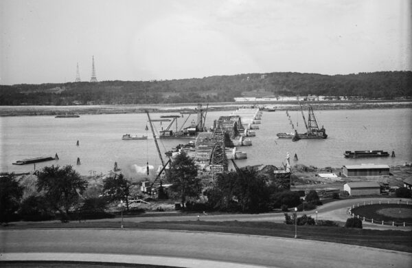 Looking east at construction on Arlington Memorial Bridge over the Potomac River in Washington, D.C., in the United States. Note the statue on the partially-constructed pedestal just to the right of the abutments (bottom center). The U.S. Commission of Fine Arts erected this mock-up to determine how high statues on the piers of the bridge should be.