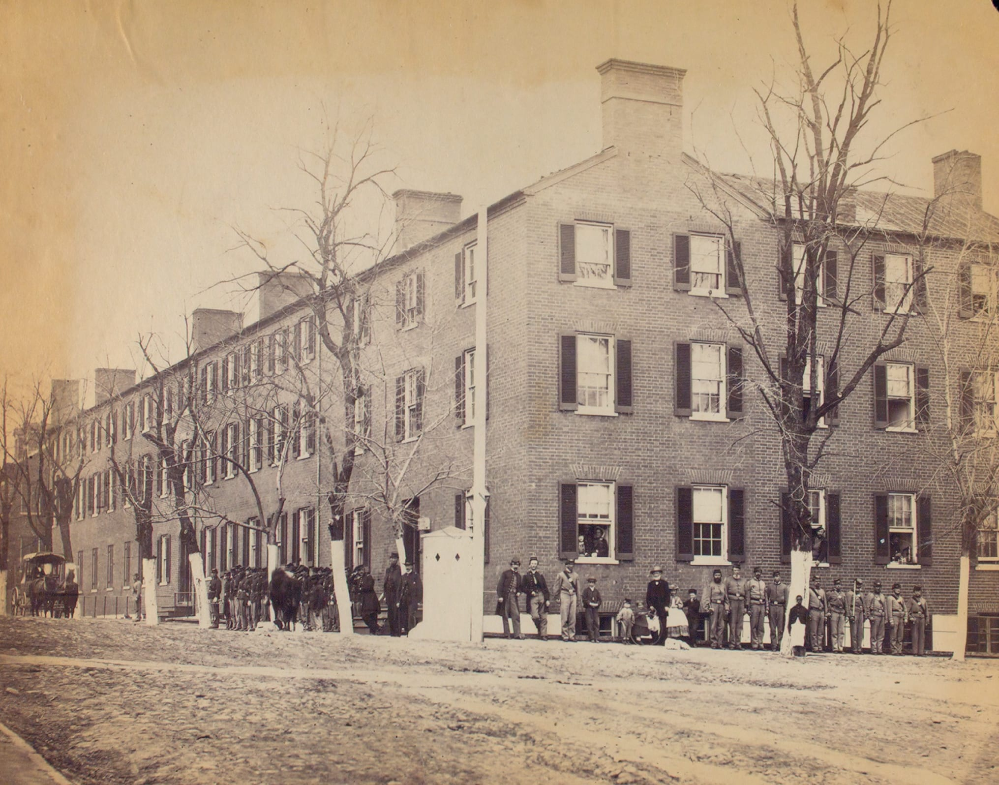 View on Pennsylvania Avenue, Washington, D.C.[Soldiers, civilians and children stand in front of a large brick corner building.]