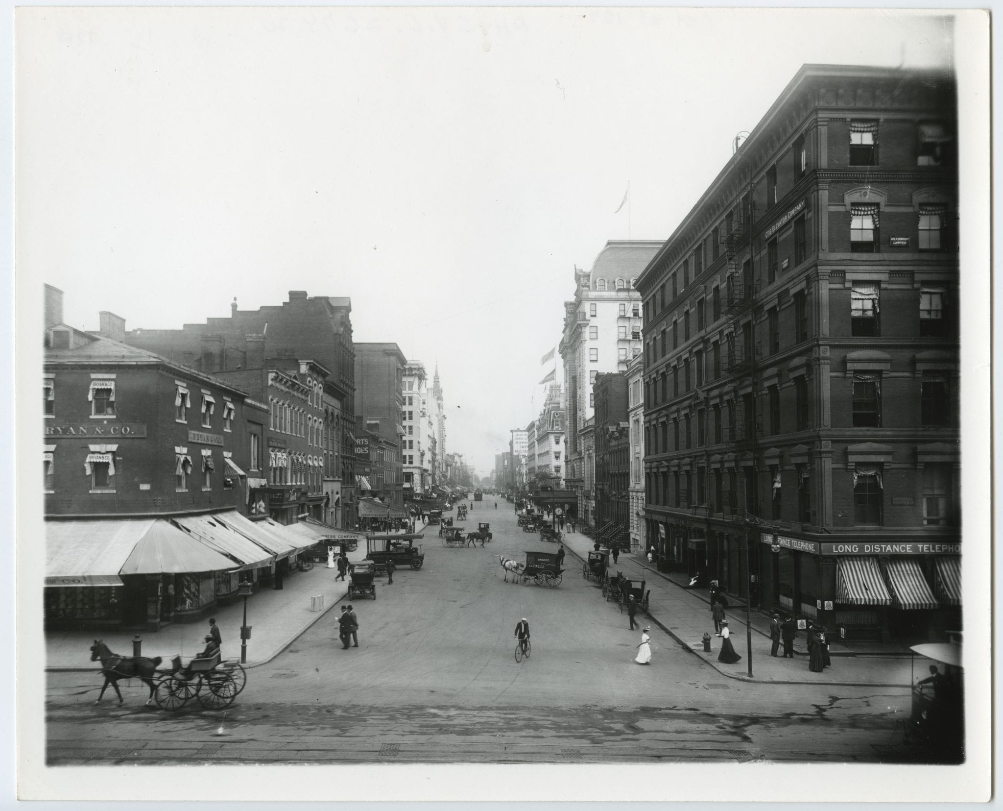 View of 15th & F Streets, NW looking east with horse carriages and a bicyclist pictured.