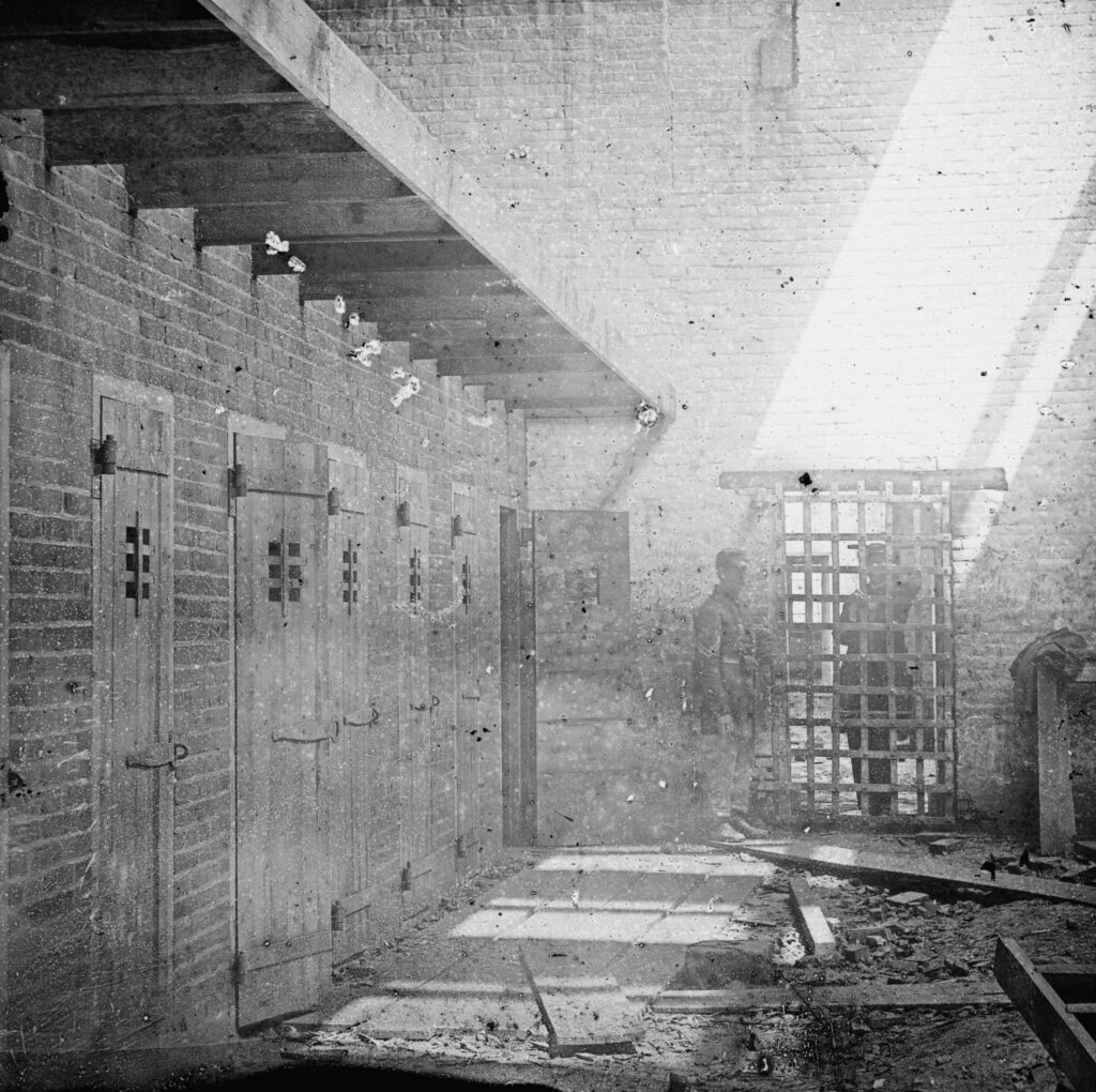 """Slave pen, Alexandria, Va."" Shows interior with slave pens at left. Across an open courtyard is a barred door with a barred door and soldier standing at left. An officer stands behind barred door. Wood debris in foreground. Five slave pens at left."