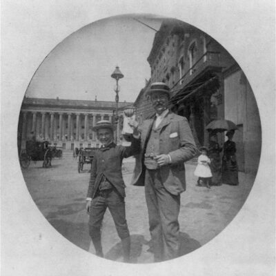 """Photo shows a man and a boy in summer straw hats happily displaying some unidentifiable papers on F Street, with the Treasury and a new electric hooded arc streetlight in the background. One of a series of scenes near Painter's office at 14th and E streets, this picture bears the hallmarks of the new """"snapshot"""" style now made possible by the invention of the quick, hand-held Kodak: natural smiles and the movement of the ladies under the umbrella."""