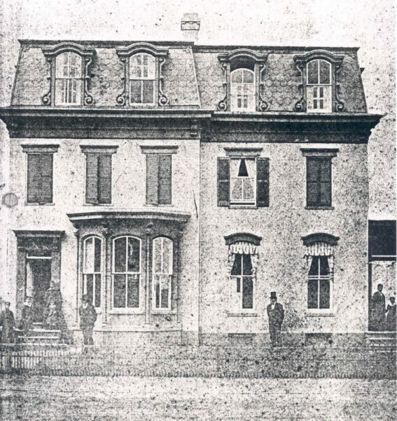 1876. Photographer: W.W. Core, Washington, D.C. Frederick Douglass is standing on the front lawn of his home on A Street, N.E., Washington, D.C. Other family members are standing out on the front porch on both side of the houses.