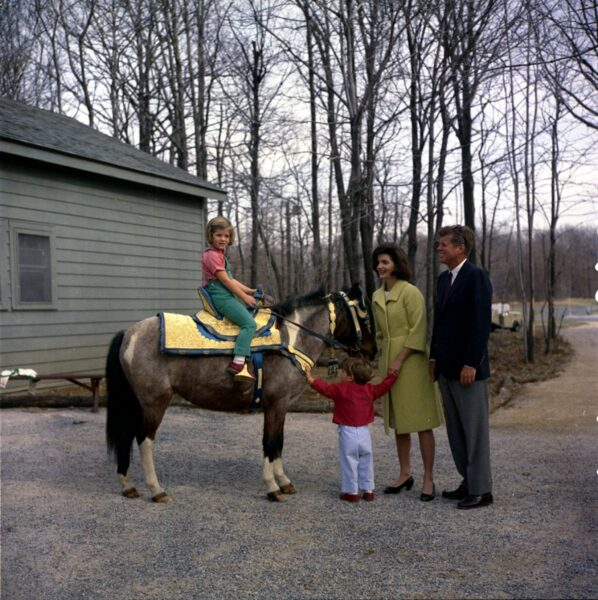 """31 March 1963 President John F. Kennedy and family watch Caroline Kennedy riding a horse named """"Tex"""" at Camp David. """"Tex"""" is wearing a blue and gold Moroccan saddle, a gift to President Kennedy from King Hassan II. Photograph includes: (L-R) Caroline Kennedy, John F. Kennedy, Jr., First Lady Jacqueline Kennedy, and President Kennedy. Camp David, Maryland. Please credit """"Robert Knudsen, White House/John F. Kennedy Presidential Library and Museum, Boston"""""""