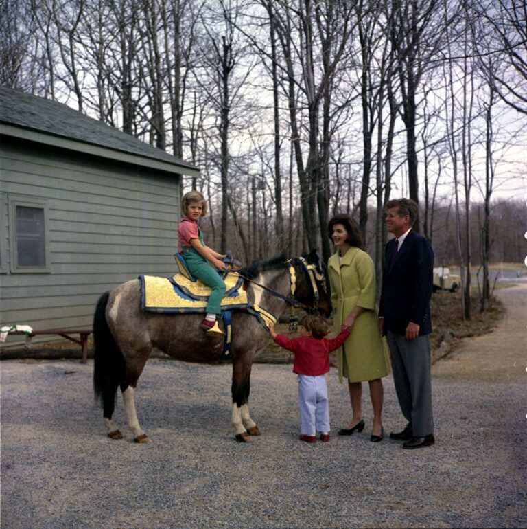 "31 March 1963 President John F. Kennedy and family watch Caroline Kennedy riding a horse named ""Tex"" at Camp David. ""Tex"" is wearing a blue and gold Moroccan saddle, a gift to President Kennedy from King Hassan II. Photograph includes: (L-R) Caroline Kennedy, John F. Kennedy, Jr., First Lady Jacqueline Kennedy, and President Kennedy. Camp David, Maryland. Please credit ""Robert Knudsen, White House/John F. Kennedy Presidential Library and Museum, Boston"""