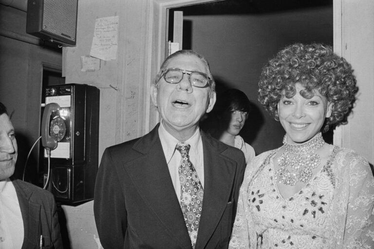 Congressman Wilbur Mills and exotic dancer Fanne Foxe speak with reporters outside Foxe's dressing room in 1974. (Bettmann Archive via Getty Images)
